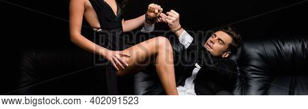 Cropped View Of Sexy Woman In Dress Pulling Handcuffs On Submissive Man Isolated On Black, Banner