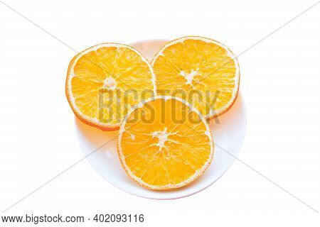 Plate With Three Slices Of Dried Orange Isolated On White Background.
