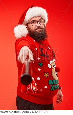 Portrait of a fat bearded man wearing Santa's hat seriously looking at the camera and threatening with a baseball bat. Red background.