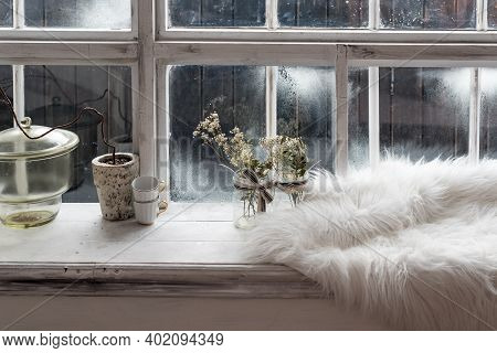 Cozy Winter Still Life. Dried Plants, Small Coffee Cups And Warm Fur On Vintage Kitchen Windowsill.