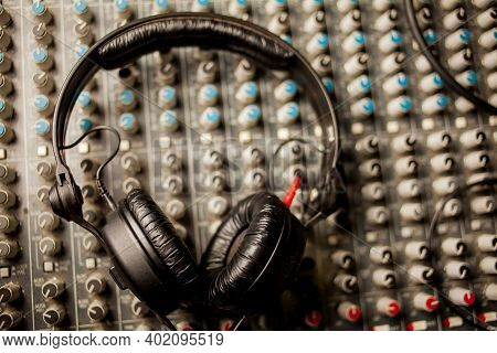 Dj Headphones Lying On The Mixer. Blue Filter. Photo For The Background. Musical Background. Backgro