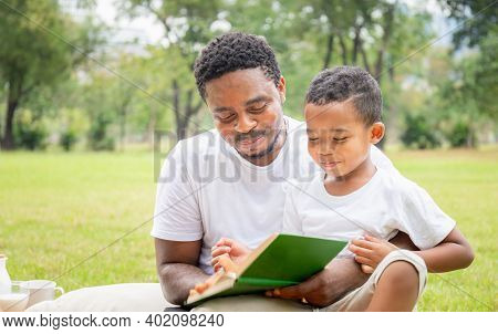 Cheerful African American Father And Son Reading A Book, Happy Dad And Son Having A Picnic In The Pa