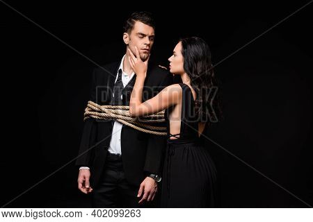 Brunette Woman In Dress Touching Face Of Tied Submissive Man In Suit Isolated On Black