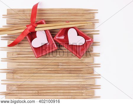 Valentine's Day Concept. Dinner Party Table. Set Of Sushi And Chopsticks Tied Red Tape On Wooden Bac