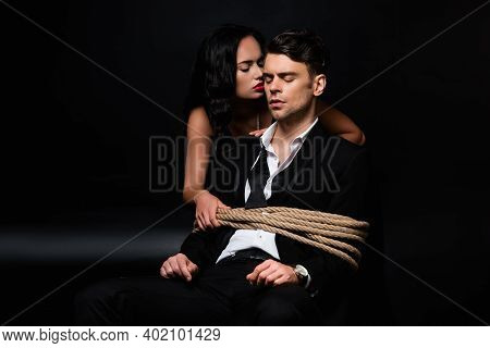 Dominant Woman In Dress Looking At Tied Submissive Man Sitting On Chair On Black