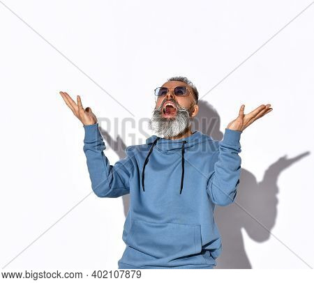 Being Fed-up Grey-haired Bearded Man In Sunglasses, Sweatshirt Looking Up And Screaming Loudly With