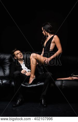 Sexy Woman In Dress Looking At Submissive Man In Handcuffs Isolated On Black