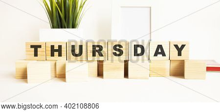 Wooden Cubes With Letters On A White Table. The Word Is Thursday. White Background With Photo Frame,