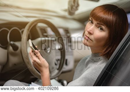 Minded Woman Driver Sitting Inside Car And Using Delivery Service On Smartphone, Part-time Job In A