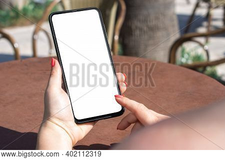 Mockup Phone. Cropped Image Of Woman Holding Smart Cell Phone At Sidewalk Cafe. Woman Texting With H