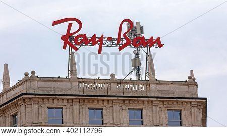 Milan, Italy - June 15, 2019: Big Red Ray Ban Sign At Top Of Building In Milan, Italy.
