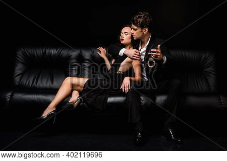 Man In Suit Holding Handcuffs Near Sexy Woman In Dress While Sitting On Sofa Isolated On Black