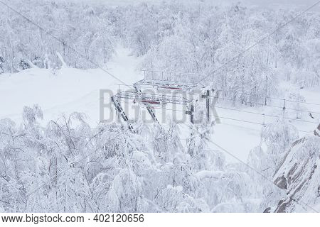 Last Tower Of The Ski Lift On A Snow-covered Hilltop Among Frosty Trees