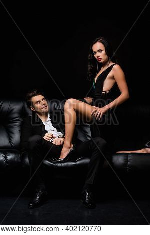 Dominant Woman In Dress Looking At Camera Near Submissive Man In Handcuffs Isolated On Black