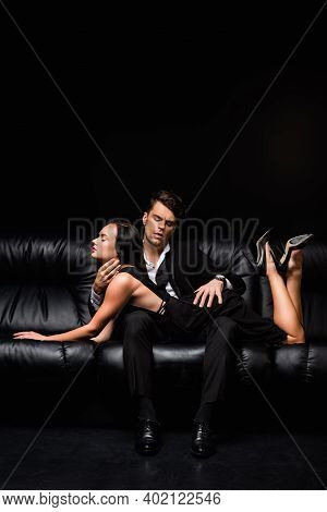Man In Suit Seducing Sexy Woman Lying On Sofa Isolated On Black