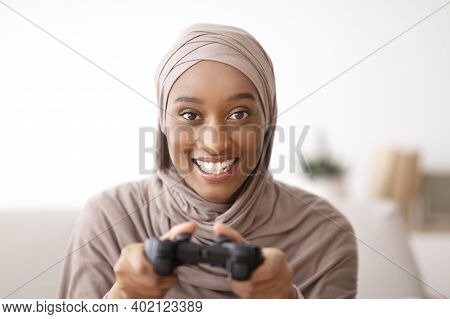 Portrait Of Happy Muslim Woman In Hijab Holding Joystick, Playing Videogame At Home. Positive Black