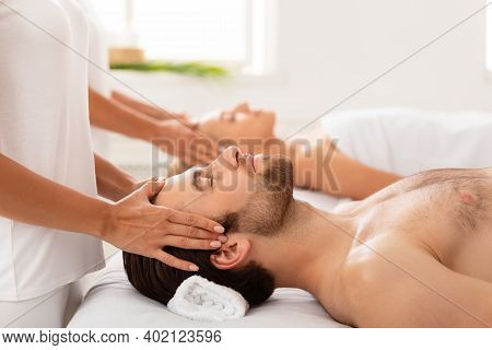 Spouses Receiving Head Massage Lying With Eyes Closed Relaxing On Beds At Spa Indoors, Focus On Husb