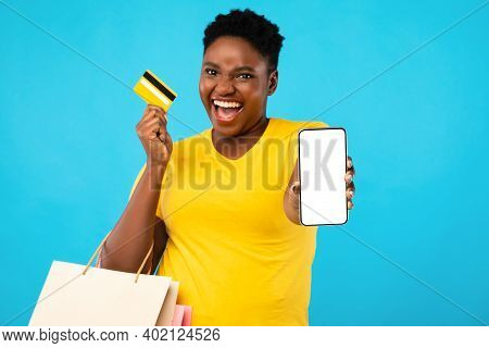 Mobile Shopping Application. Excited Black Woman Showing Smartphone Empty Screen Holding Credit Card