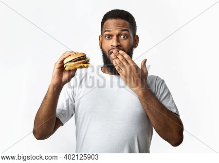 Oops, Cheat Meal. Funny African Guy Holding Unhealthy Burger Covering Mouth Posing Standing On White