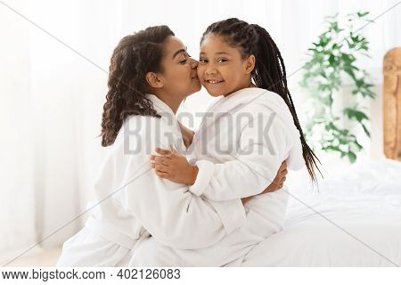 Mothers Love. Loving Black Mom Kissing Her Cute Little Daughter While Relaxing In Bathrobes On Bed A