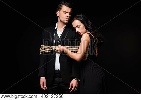 Dominant Woman In Dress Standing With Tied Submissive Man In Suit Isolated On Black
