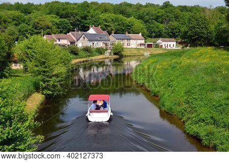 Pleasure Boat Sailing In Green Surroundings On The River Yonne In Burgundy, France
