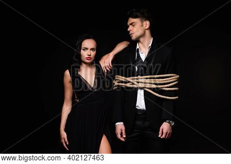 Brunette Woman In Dress Standing With Tied Submissive Man Isolated On Black
