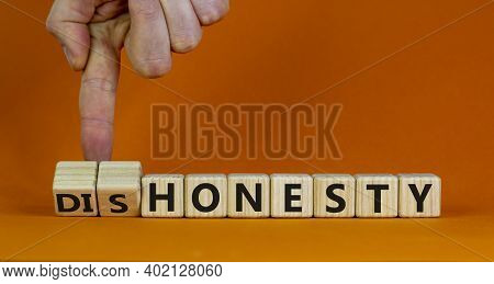 Honesty Or Dishonesty Symbol. Businessman Hand Turns A Cube And Changes The Word 'dishonesty' To 'ho
