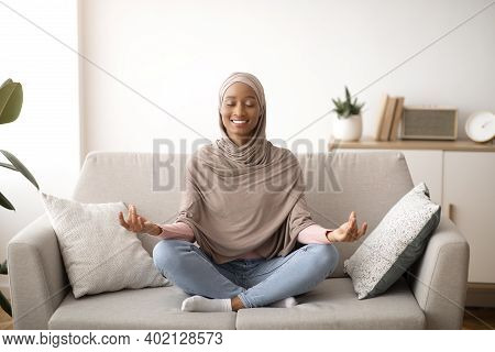 Stress Management Concept. Peaceful Young Lady In Hijab Meditating With Closed Eyes On Sofa At Home.