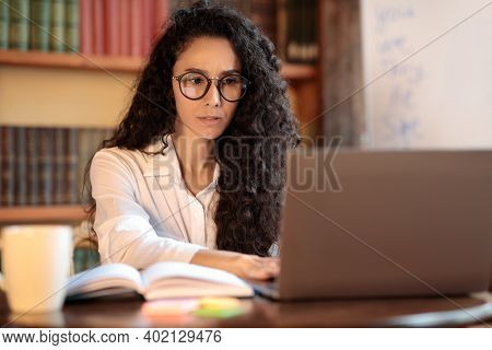 Portrait Of Pensive And Confused Woman In Eyeglasses Using And Working On Computer, Typing On Laptop