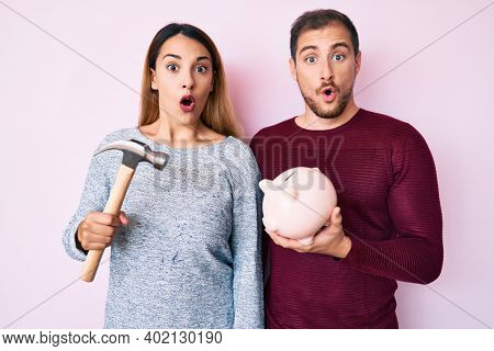 Beautiful couple holding piggy bank and hammer scared and amazed with open mouth for surprise, disbelief face