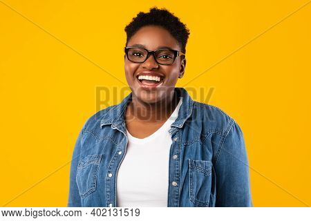 Cheerful African Plus-size Woman Smiling To Camera Posing Standing Over Yellow Studio Background, We