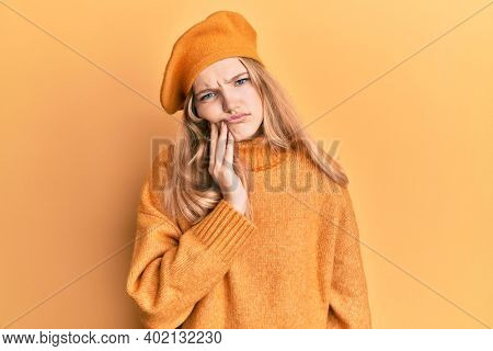 Beautiful young caucasian girl wearing french look with beret touching mouth with hand with painful expression because of toothache or dental illness on teeth. dentist