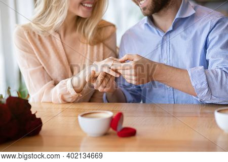 Cropped View Of Millennial Guy Holding His Fiancees Hand With Diamond Engagement Ring At Cafe. Young