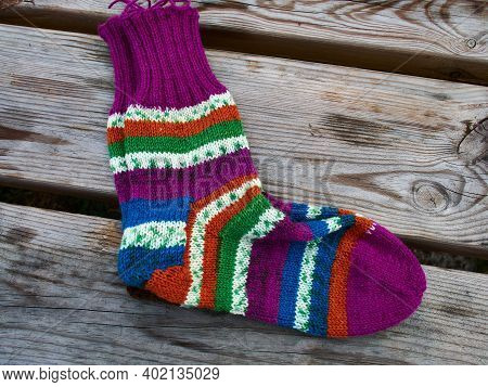 Handcrafted Handmade And Knitted Knitwear Traditional Colorful Socks Laid On A Wooden Table
