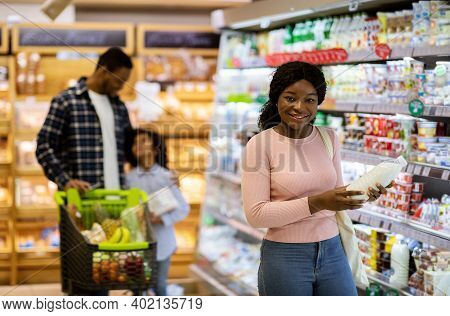 Happy Black Family With Child Shopping For Products At Dairy Section Of Supermarket, Copy Space. Pos