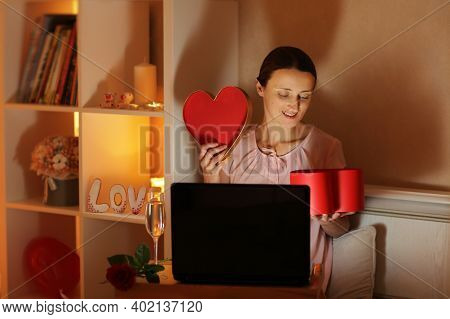 The Girl Communicates Via Video Link With Her Beloved And Opens The Received Gift Box In The Evening