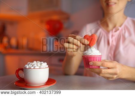 A Girl In Love Prepares Cupcakes For A Loved One For Valentine's Day, Decorating The Dessert With A