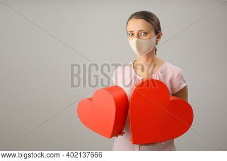 A Girl In A Medical Mask Holds Two Large Red Hearts In Her Hands, Copy Space