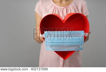 Disposable Medical Mask On A Big Red Heart. The Concept Of Care And Love