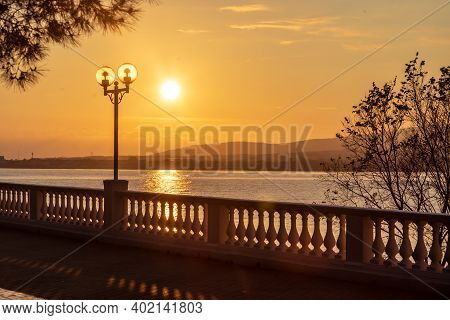 Summer Sunset In Golden Tones. Silhouette Of A Balustrade. Shadow Of The Balustrade On The Embankmen