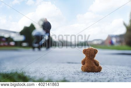 Rear View Lonely Teddy Bear Doll Sitting Alone On Hailstones With Blurry Father Pushing Stroller Wal