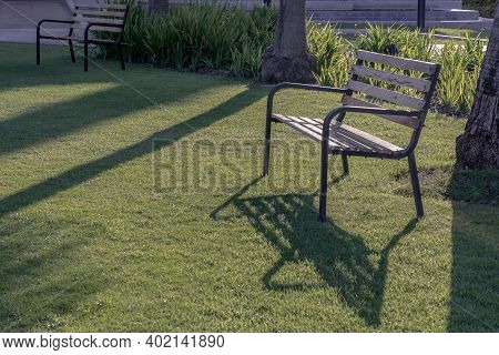 Wooden Benches On Grass Floor In A Shady Area Of The Park. Seating And Unwind Area. Selective Focus.