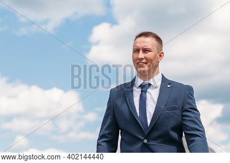 Lifestyle Portrait Of Happy Groom Outdoor At Nature With Sky And Clouds On Background. Cheerful Fian