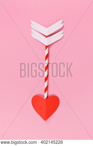 Paper Cupid Love Arrow With Heart Shaped Tip On Pink Background