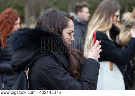 Russia, Saint Petersburg 20.04.2019: A Young Female Tourist In The Crowd Takes Photos Of Sights On T
