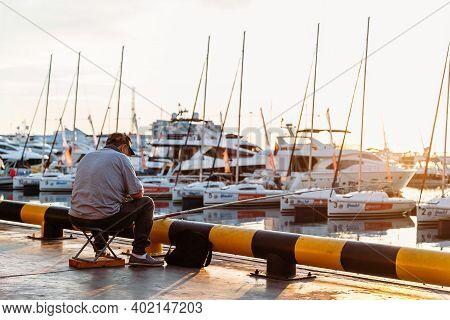 Sochi, Krasnodar Territory, June 5 2018, Fisherman Fishing At Seaport In Sochi Against Background Of
