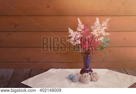 Red And Pink Beautiful Astilbe Flowers In Blue Vase And Decorative Balls On Wooden Table. Selective