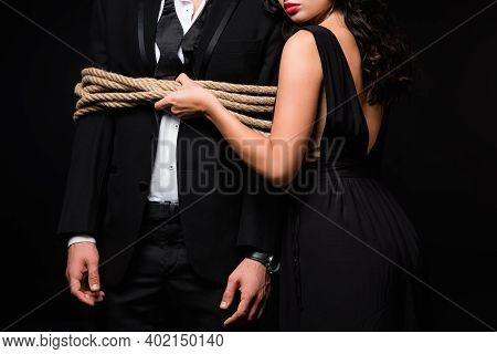Cropped View Of Dominant Woman In Dress Standing With Tied Submissive Man In Suit Isolated On Black