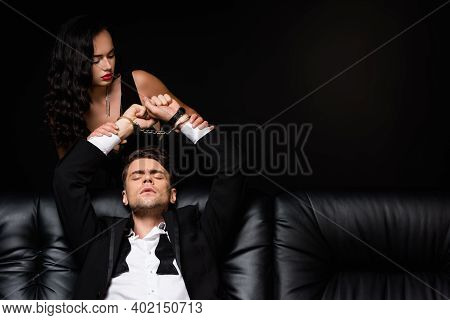 Sexy Woman In Dress Looking At Submissive Handcuffed Man With Closed Eyes Isolated On Black